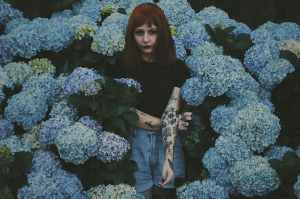 woman with black and red flower tattoo standing behind blue flowers