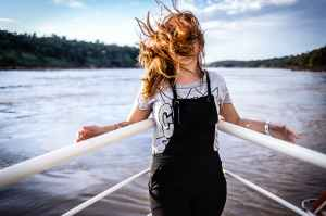 woman wearing gray shirt and black overalls on boat
