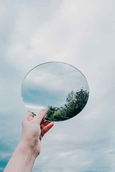 person holding round frame less mirror